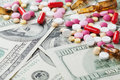 Heap of pharmaceutical drug and medicine pills scattered on dollar cash money, cost medicinal product and treatment concept