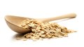 Heap of rolled oats with wooden spoon on white Royalty Free Stock Photography
