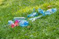 Heap of rubbish on grass in park littering of environment sunny plastic and glass bottles bottle caps and paper concept Stock Photography