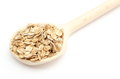 Heap of rye flakes with wooden spoon on white background Royalty Free Stock Photo