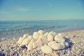 Heap of white pebbles on pebbly beach; faded, retro style