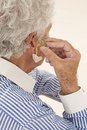 Hearing aid on senior man closeup of a inserting a in her hear focus the Royalty Free Stock Photo