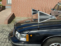 Hearse car front of with two black flags Stock Photos