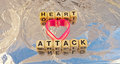 Heart attack text in black upper case letters on small white cubes with pink shape on reflecting background Stock Photo