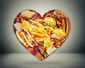 Heart and bad diet stroke risk concept health shaped of fast junk fatty food Stock Images