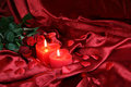 Heart candles with three red roses rose on satin background Stock Photography