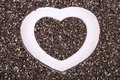 Heart in chia close up background of organic seeds with white wood shaped frame inside Stock Photography
