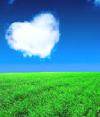 Heart from clouds and green field Royalty Free Stock Images