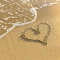 Heart drawn in beach sand, gentle surf wave. Love. Royalty Free Stock Photo