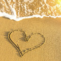 Heart drawn in beach sand soft wave and solar glare love Royalty Free Stock Photography