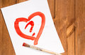 The heart drawn with red paint on a clean sheet of paper with a Royalty Free Stock Photo