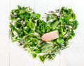 Heart formed of fresh culinary herbs assorted green including parsley thyme rosemary basil and chives with a blank brown gift tag Stock Photography