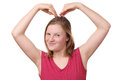 Heart gesture portrait of a teenage girl doing a with her hands on white background Royalty Free Stock Photography
