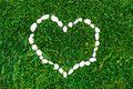 Heart on the grass lined with stones. Valentine`s day. Romantic concept. Background