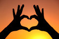 Heart hands silhouette of a woman s forming a perfect against a orange sunset sky Royalty Free Stock Images