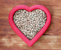 Heart healthy lentils brown in red shape isolated on wood Stock Photography