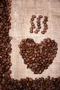 Heart illustration made of fresh aromatic coffee beans on cloth vintage background with frame Royalty Free Stock Photos