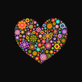 Heart laid out various flowers of different colors on black Royalty Free Stock Photo