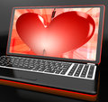 Heart on laptop showing cupid shot or passion Stock Image