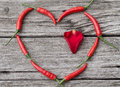 Heart made of chili pepper with rose petal inside on wooden background Royalty Free Stock Photography