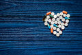 Heart made of pills on blue wooden table background top view copyspace