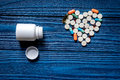 Heart made of pills and pill bottle on blue wooden table background top view copyspace