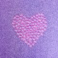 Heart made of pink plastic hearts on a purple glittering background Royalty Free Stock Photo