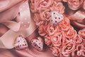 Heart made of pink roses with ribbons and chocolates on satin Royalty Free Stock Photos