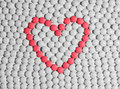 Heart made of tablets red pills on a background white pills Royalty Free Stock Image