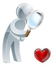 Heart magnifying glass man a person holding a and looking at a shaped symbol could be concept for looking for love or dating or Stock Image