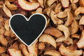 Heart pointer, the price tag lies on dried apple Royalty Free Stock Photo