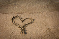 Heart on sand beach drawing of a sandy with water Stock Image