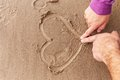 Heart on a sand couple drawing hearts wet Stock Image