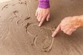 Heart on a sand couple drawing hearts wet Stock Photography