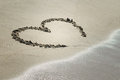 Heart on sand with wave approaching Stock Image