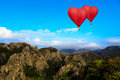 Heart shape ballooning flying over mountain Royalty Free Stock Photo