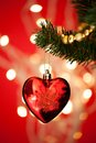 Heart shape bauble on christmas tree close up of Stock Image