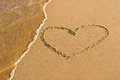 Heart shape drawing in the sand waves washing away Royalty Free Stock Photography