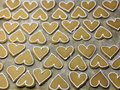 Heart shape ginger biscuits rows of shaped on a baking tray decorated with icing to edges Royalty Free Stock Photography