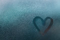 Heart shape on glass with water drops is painted in rainy weather Royalty Free Stock Photo