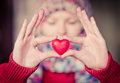 Heart shape love symbol in woman hands with face on background valentines day romantic greeting people relationship concept winter Royalty Free Stock Photos