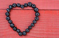 Heart shape made from blueberries the of a on a red wood background horizontal format with copy space Stock Photo