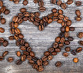 Heart shape made from coffee beans on wooden background this high quality photograph reprersents Stock Photography