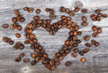 Heart shape made from coffee beans on wooden background this high quality photograph reprersents Royalty Free Stock Image