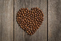Heart shape made from coffee beans on wooden table Royalty Free Stock Image