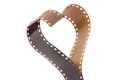 Heart shape made from mm negative film strip a camera on white Royalty Free Stock Photography