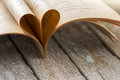 Heart shape from opened book pages on wood background. Royalty Free Stock Photo