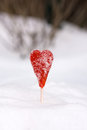Heart shape red lollipop in the snow Royalty Free Stock Photos