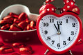 Heart shape red love clock and chocolates Royalty Free Stock Photo