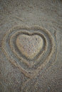 Heart shape in the sand on the beach. Top view. Vertical. Royalty Free Stock Photo